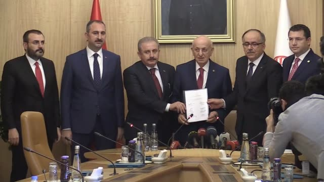 Turkish Parliament Speaker Ismail Kahraman receives a bill bearing the signature of Prime Minister Binali Yildirim and opposition MHP leader Devlet...