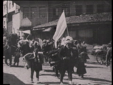 stockvideo's en b-roll-footage met turkish people returning to trabzon families walking back home carrying heavy luggage on their backs through streets / trabzon turkey - 1915