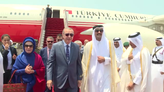 Turkish President Recep Tayyip Erdogan and his wife Emine Erdogan are welcomed by Qatari Emir Sheikh Tamim bin Hamad Al Thani upon their arrival at...