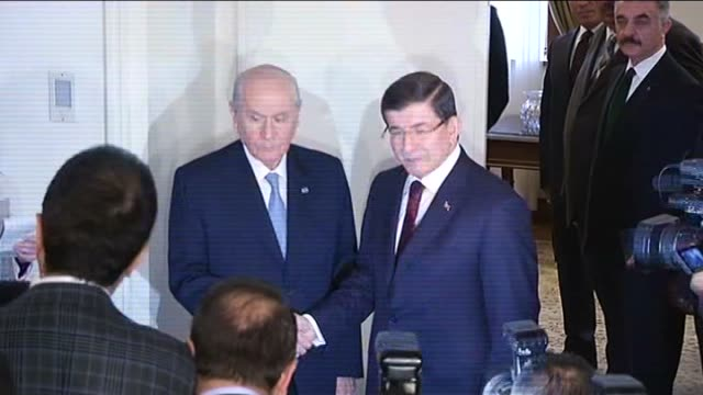 turkish prime minister ahmet davutoglu is welcomed by opposition nationalist movement party leader devlet bahceli prior to their meeting at the grand... - primo ministro turco video stock e b–roll