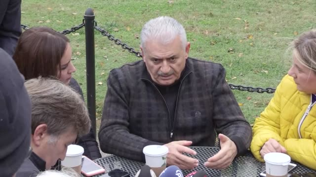 turkish prime minister binali yildirim accompanied by turkish foreign minister mevlut cavusoglu answers the questions of journalists as he walks out... - binali yildirim stock-videos und b-roll-filmmaterial