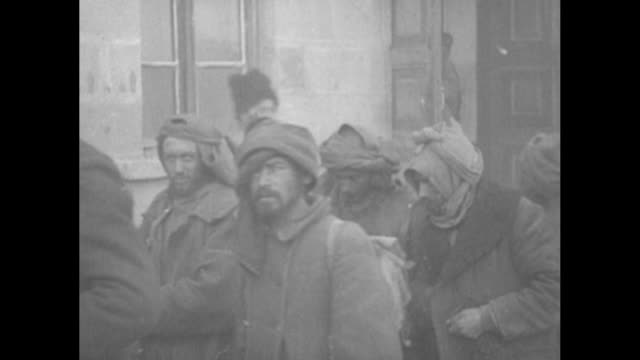 turkish prisoners of war pass camera as they walk by building / turkish pows pass camera as they walk across snow / note exact year not known... - prisoner stock-videos und b-roll-filmmaterial