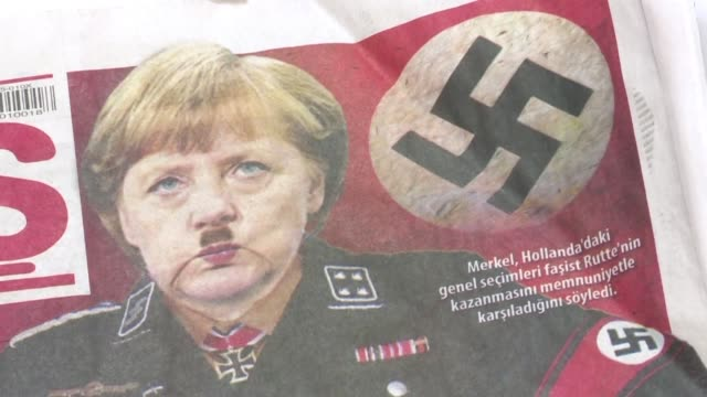 vídeos de stock e filmes b-roll de a turkish pro government newspaper depicts chancellor angela merkel on its front page in nazi uniform with a hitler style moustache labelling the... - frau