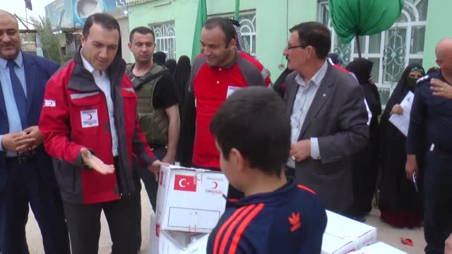 turkish red crescent members distribute humanitarian aids to the iraqi refugees who fled their homes due to daesh terrorists attack at tal afar and... - najaf stock-videos und b-roll-filmmaterial