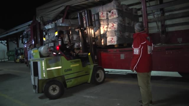 Turkish Red Crescent members load humanitarian aid packages into trucks to be distributed to quake victims in northern Iraq on November 13 2017 in...