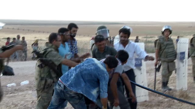 turkish security forces stand guard as syrians, fled from clashes between the islamic state of iraq and levant militants and democratic union party... - isil konflikt stock-videos und b-roll-filmmaterial