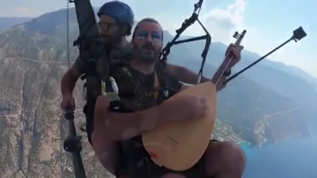 turkish singer performed paragliding in southwestern turkey with the baglama a stringed instrument closely linked to anatolian turkey up in the sky... - mugla province stock videos & royalty-free footage