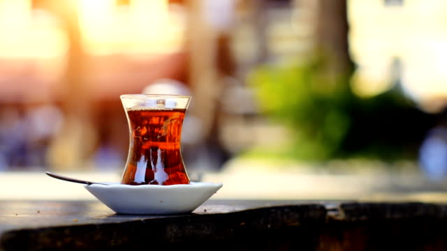 turkish tea with special cup on a sidewalk tea house table with unrecognizable blurry people on the background - black tea stock videos & royalty-free footage