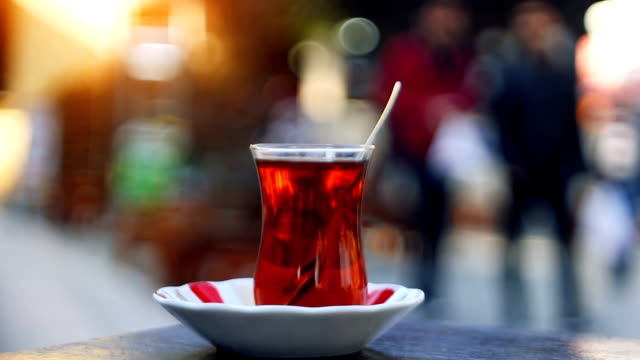 vídeos de stock e filmes b-roll de turkish tea with special cup on a sidewalk tea house table with unrecognizable blurry people on the background - chávena de chá