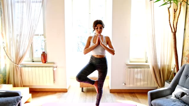 turkish woman doing yoga and stretching at home in the living room - balance stock videos and b-roll footage