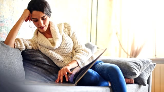 turkish woman reading a magazine on the couch - magazine publication stock videos & royalty-free footage