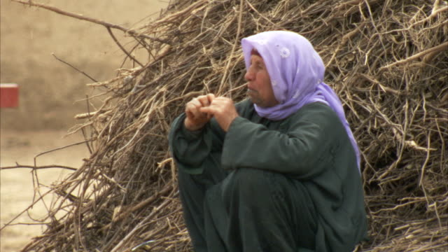 turkish woman sits beside a stack of hay. - hay stack stock videos & royalty-free footage