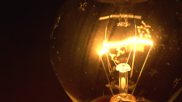turn on bulb on black background - old lightbulb stock videos and b-roll footage
