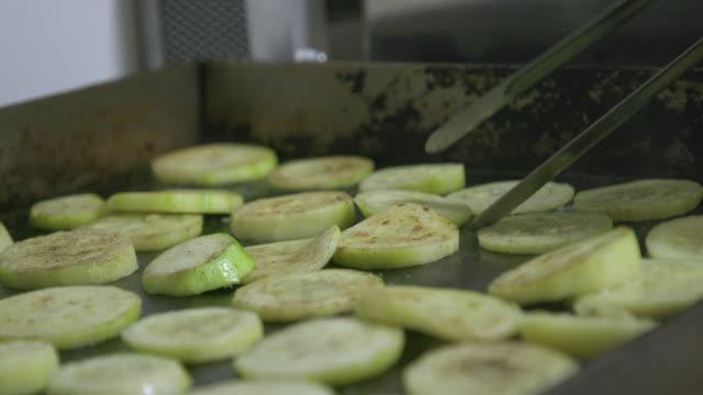 vidéos et rushes de en tournant les courgettes frites tranches sur cuisinière haut de la page - vapeur