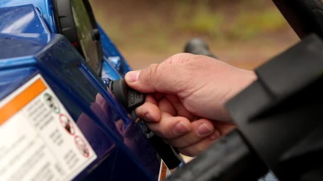 turning key on four wheeler to start engine - endast en medelålders man bildbanksvideor och videomaterial från bakom kulisserna