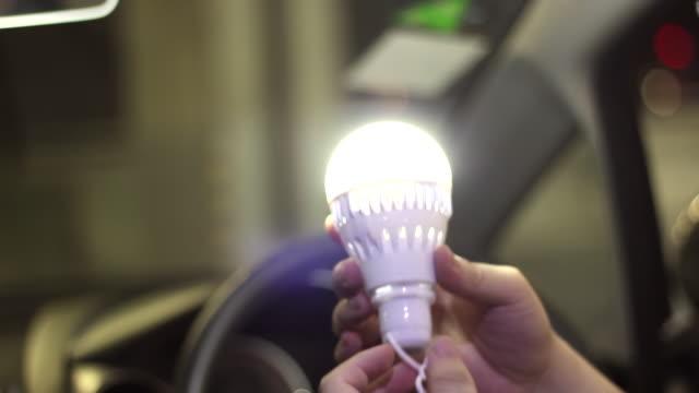 glühbirne drehen im auto - led leuchtmittel stock-videos und b-roll-filmmaterial