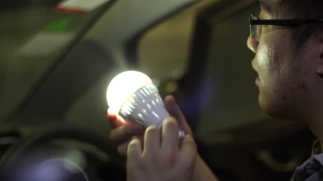 vídeos de stock, filmes e b-roll de transformando a lâmpada no carro com o telefone de tela verde - luz de led