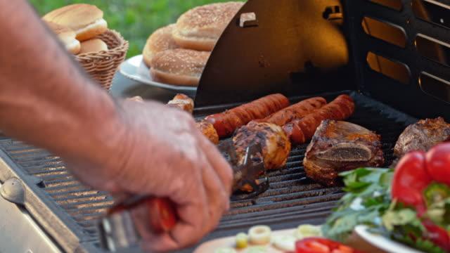 vídeos y material grabado en eventos de stock de girando la carne a la parrilla con pinzas - 65 69 años