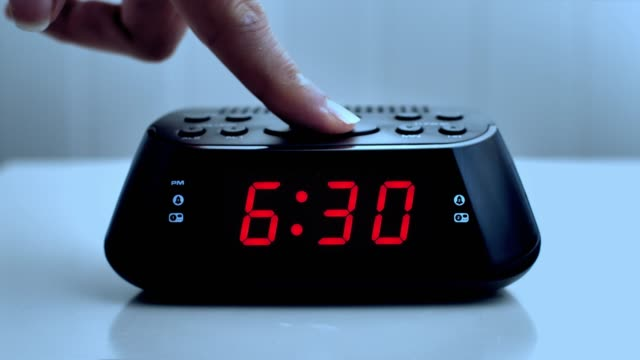 vídeos de stock e filmes b-roll de turning off a digital alarm clock, time from 6.29 to 6.30. woman's hand. - acordar