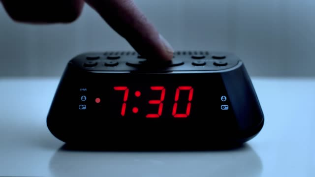 turning off a digital alarm clock, time from 7.29 to 7.30. - changing clock stock videos and b-roll footage