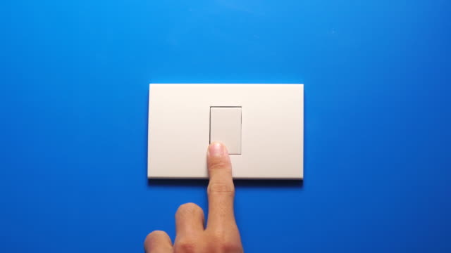 vídeos de stock e filmes b-roll de turning off light bulb switch on blue wall - turning