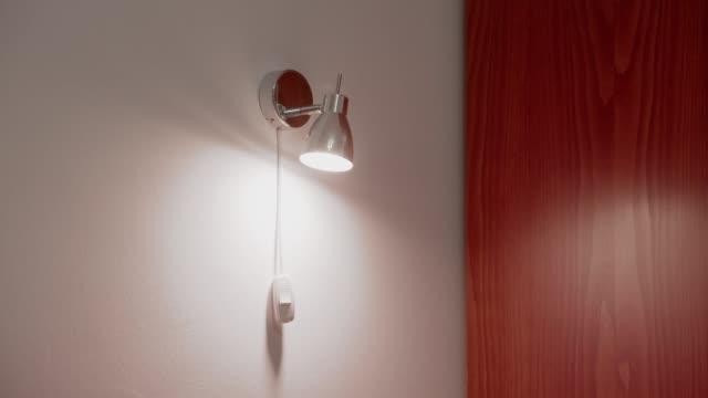 einschalten einer led-glühbirne lampe, moderne wandleuchte. - led leuchtmittel stock-videos und b-roll-filmmaterial