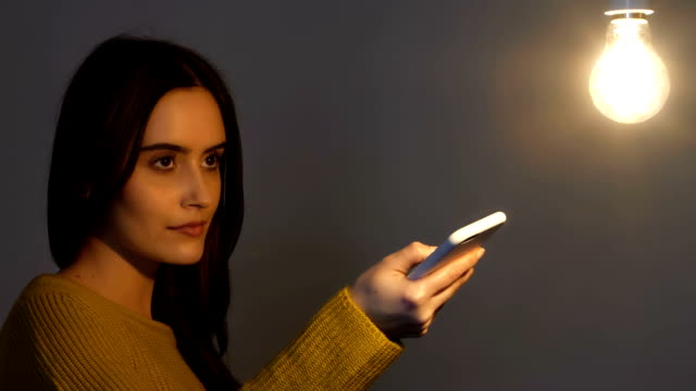 turning on an electric light, phone app. - lampada elettrica video stock e b–roll