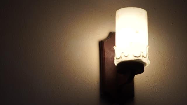 vidéos et rushes de allumer/éteindre le mode électrique lampe accroché sur le mur - turning on or off