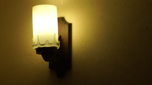 turning on and off old fashion electric lamp hanging on wall - low lighting stock videos & royalty-free footage