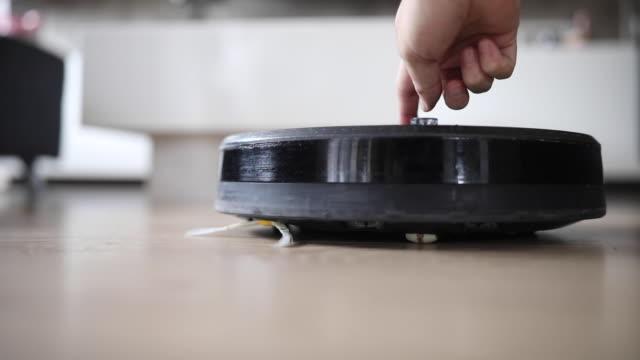 vídeos de stock e filmes b-roll de turning on robotic vacuum cleaner - limpar o pó