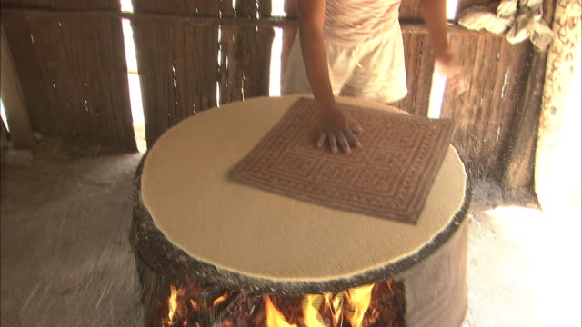 Turning Over Cassava (Yucca) Flour Cake In The Village Of Santa Marta, Colombia