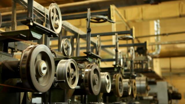 stockvideo's en b-roll-footage met turning pulleys in an enameled copper wire factory - machinekamer