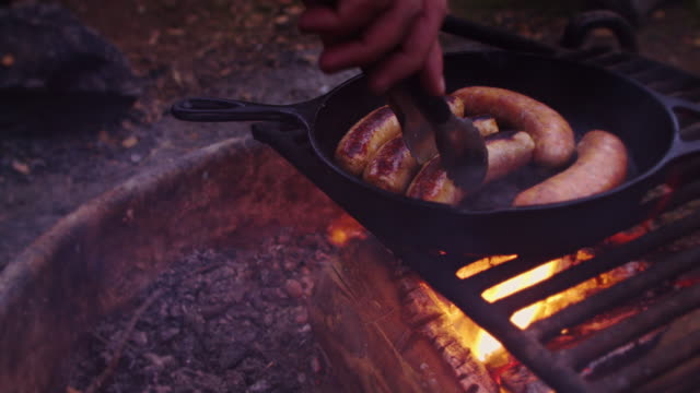 turning sausages cooking on campfire - cast iron stock videos & royalty-free footage