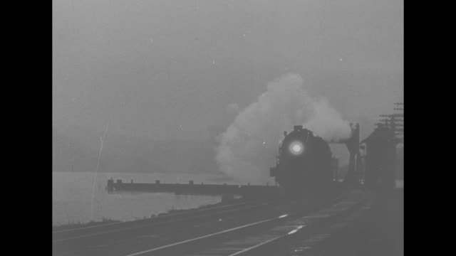 turning wheels of a locomotive / vs high angle view of train engine locomotive rolling past with the new york city skyline in the distance and snow... - yard measurement stock videos and b-roll footage