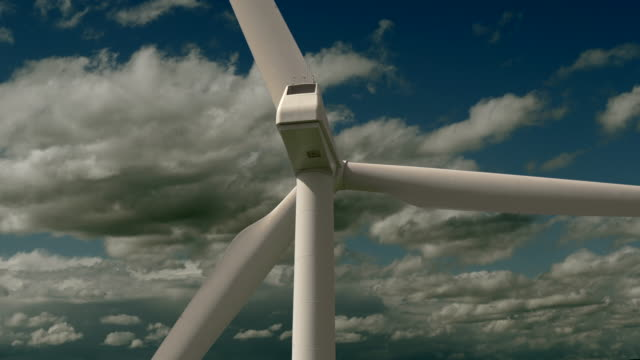 turning wind turbine with blue sky and cloudscape background with fast moving clouds - turbine stock-videos und b-roll-filmmaterial