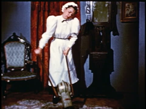 1950 reenactment turn-of-century maid pumping early vacuum cleaner device in living room - collaboratore domestico video stock e b–roll