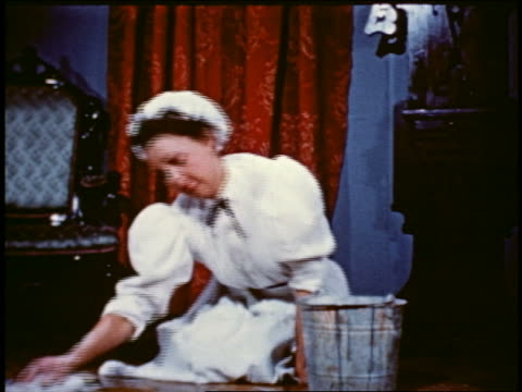 1950 reenactment turn-of-century maid scrubbing floor with sponmge + metal pail - collaboratore domestico video stock e b–roll