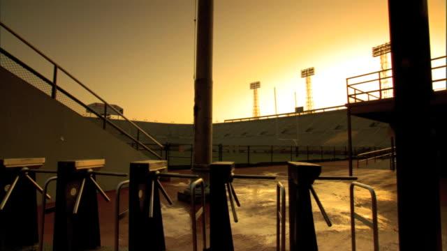 vídeos de stock e filmes b-roll de turnstiles w/ empty stadium field & bright white sunlight bg. surreal, no people, college, professional, sports. - torniquete divisa