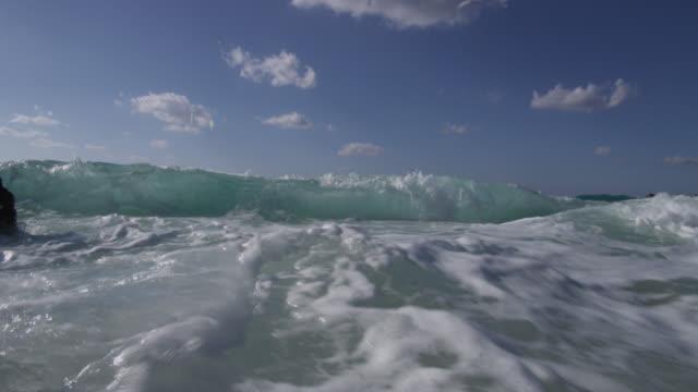 vidéos et rushes de turquoise breaker splashes over camera, bahamas - écume