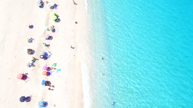 turquoise ocean and some tourists on the beach - slovenia stock videos & royalty-free footage