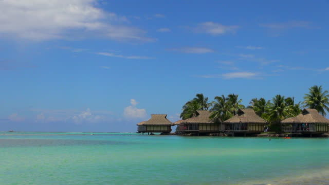 Turquoise Ocean Water with Huts and Tourists