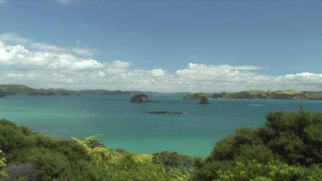 ws ha  turquoise sea with small islands surrounded by lush coast, bay of islands, new zealand - bay of islands new zealand stock videos & royalty-free footage