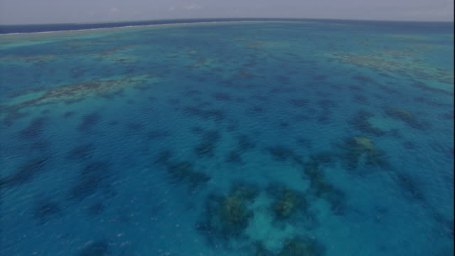 Turquoise water flows over shallow corals in the Great Barrier Reef. Available in HD.