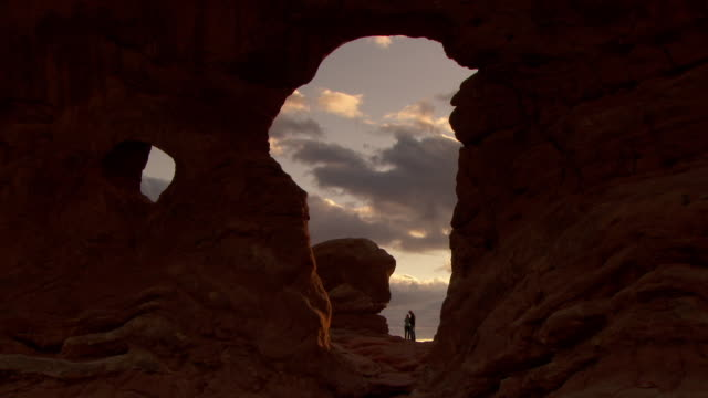 turret arch with a couple silhouetted against dramatic cloudy sunset sky - arches national park stock videos & royalty-free footage