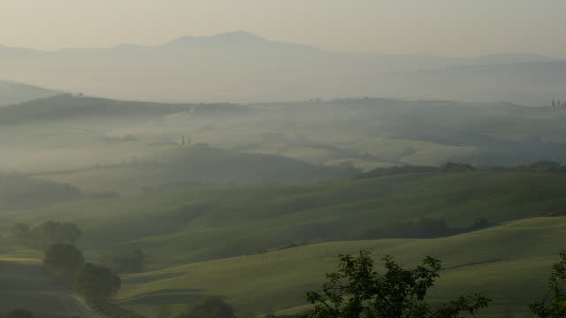 Tuscany, Tuscany, series of foggy hills with a farm at sunrise, panning left.