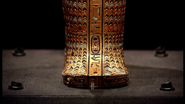 vidéos et rushes de tutankhamun exhibition at the o2 items displayed in room with subdued lighting / highly decorated and gilded sarcophagus of tutankhamun - exposition et salon professionnel