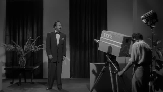 tv show host talking on a tv station set with vintage cameras and a camera operator - 電視節目 個影片檔及 b 捲影像