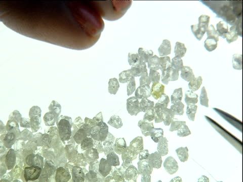 vidéos et rushes de tweezers and fingers sorting through pile of rough diamonds - diamant