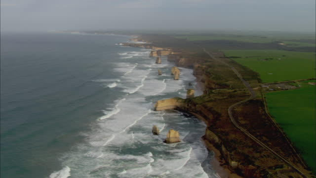 ws aerial twelve apostles with waves forming and crashing, melbourne, victoria, australia - 石灰岩点の映像素材/bロール
