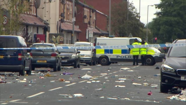 Twelve injured at street party shooting in Moss Side area of Manchester ENGLAND Manchester Moss Side EXT General view police cordon across street...